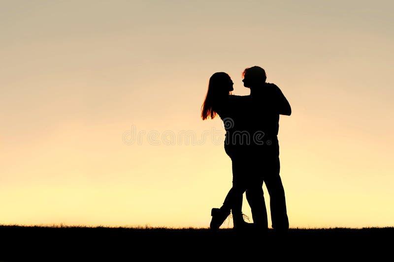 愉快的年轻夫妇跳舞剪影在日落的 库存图片