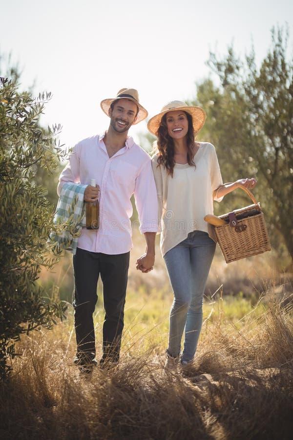 愉快的年轻夫妇运载的野餐篮子画象  免版税库存照片