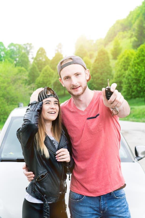 愉快的年轻夫妇,做selfie的朋友,当坐在汽车时 新的成人 白种人人民 背景在飞机运输白色的概念地球 库存照片