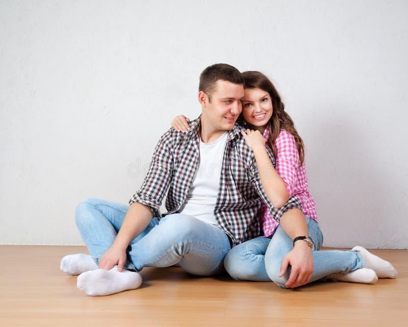 愉快的年轻夫妇画象坐查寻的地板 免版税库存图片