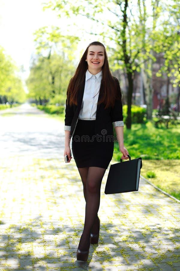 愉快的年轻女商人在城市公园走 免版税图库摄影