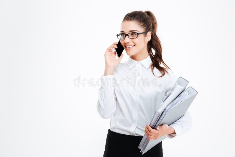 愉快的年轻女实业家拿着文件夹和谈话在手机 免版税库存图片