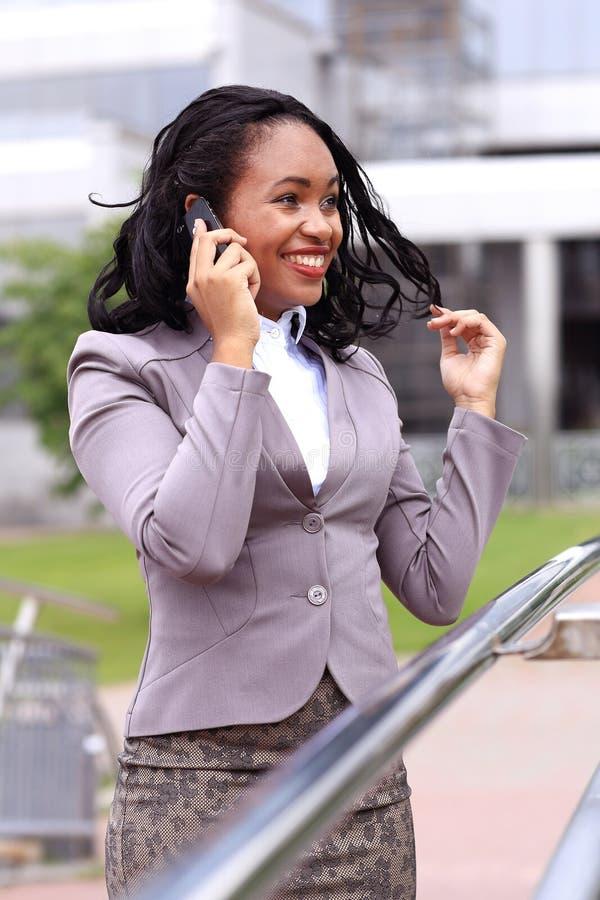 愉快的年轻女实业家谈话在手机 库存照片