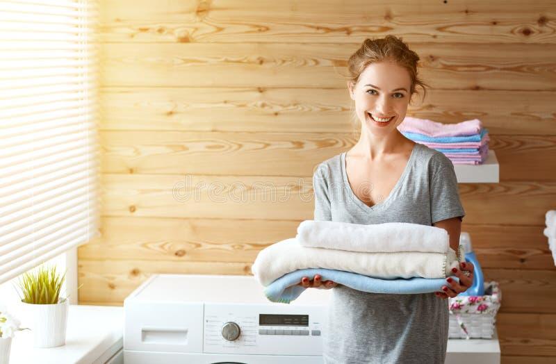 愉快的主妇妇女在有洗衣机的洗衣房 免版税图库摄影