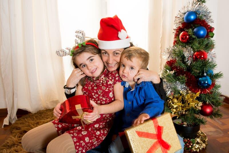 愉快的年轻妈咪、儿子和女儿圣诞节的 免版税图库摄影