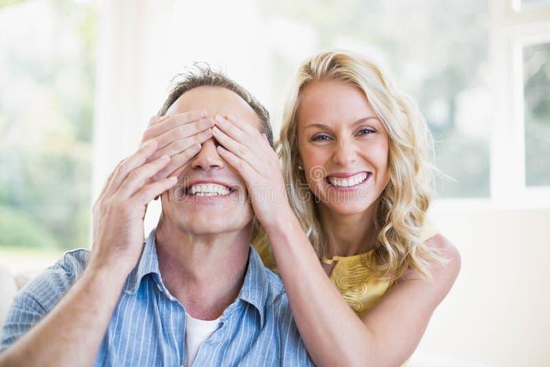 愉快的妻子覆盖物丈夫眼睛 免版税库存图片