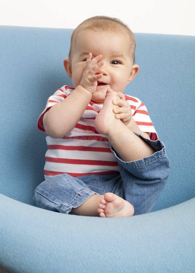 愉快的婴孩的出牙用她的手 库存照片