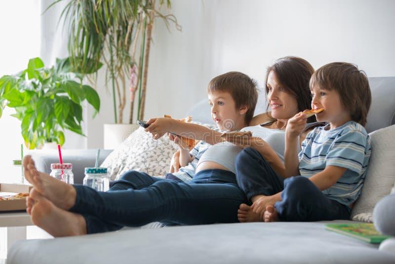 愉快的年轻家庭、怀孕的母亲和两个男孩,吃鲜美p 库存图片