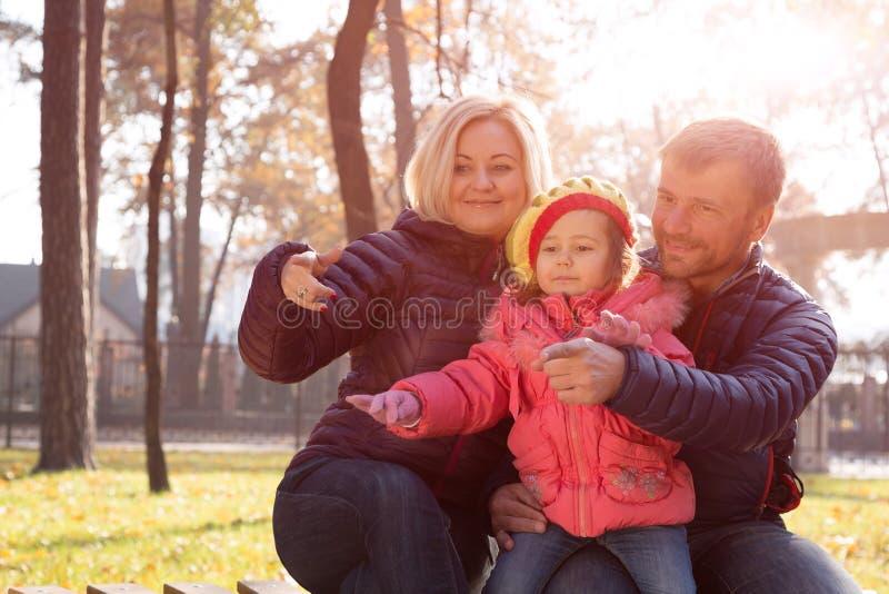 愉快的年轻家庭一起在提出观点的公园姿态 库存照片