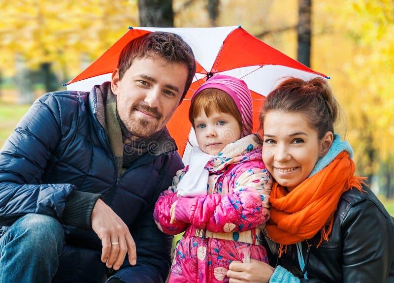 愉快的年轻家庭在伞下 库存图片