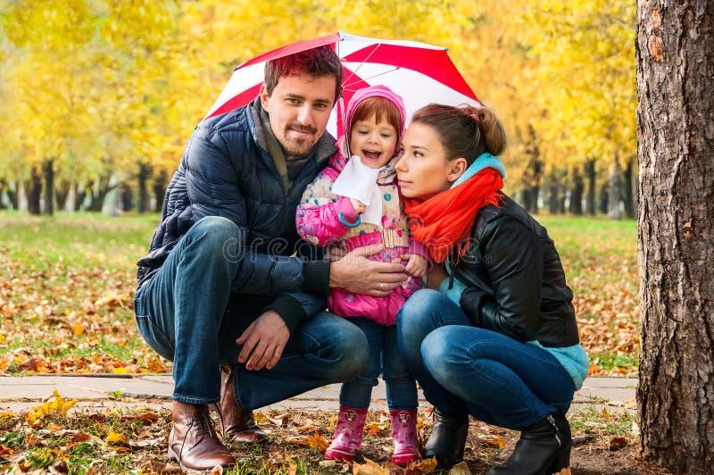 愉快的年轻家庭在伞下 免版税库存照片