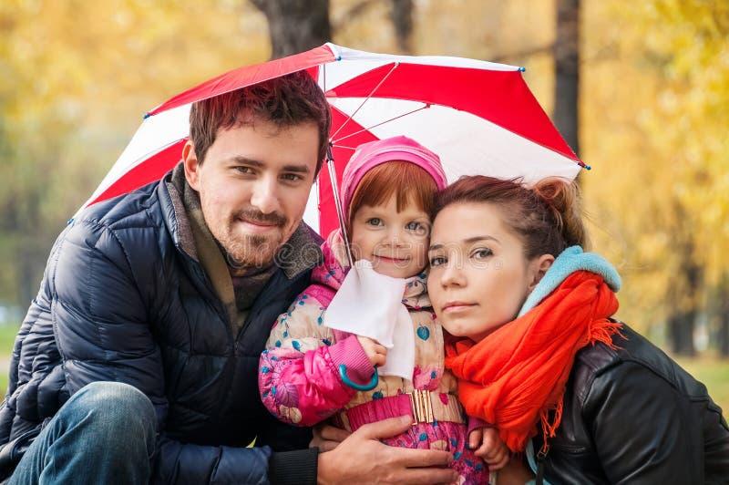愉快的年轻家庭在伞下 免版税库存图片