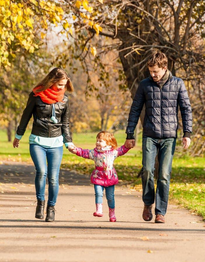 愉快的年轻家庭在公园走 免版税库存图片