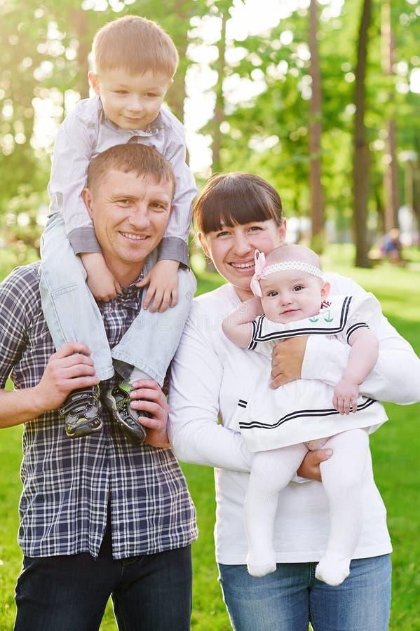 愉快的年轻家庭在夏天公园走 免版税库存照片