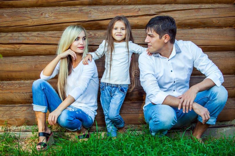 愉快的年轻家庭在木房子附近坐 库存照片