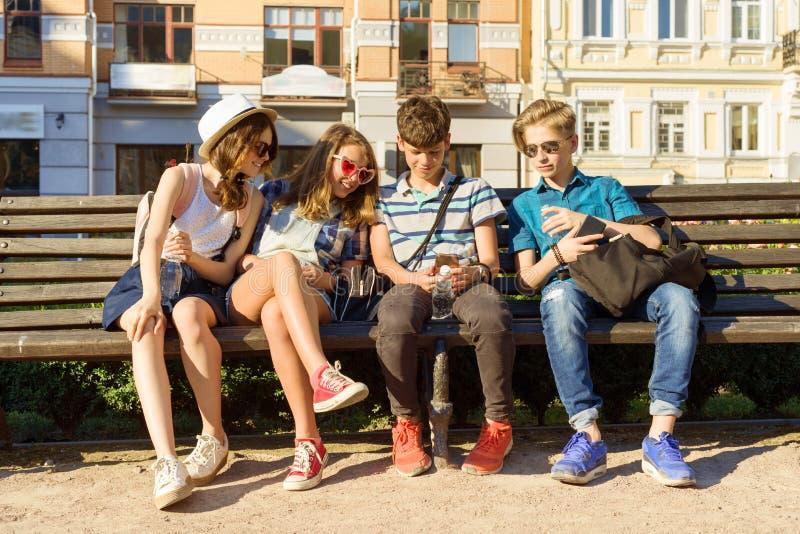 愉快的4少年朋友或高中生获得乐趣,谈话,读电话在城市在长凳 友谊和人们 免版税库存照片