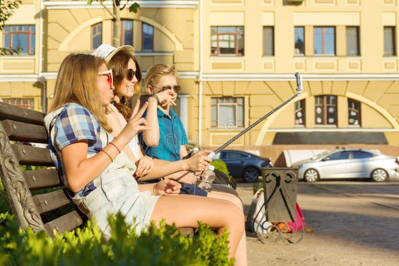 愉快的4少年朋友或高中生获得乐趣,谈话,读电话,做selfie照片在城市在长凳 免版税库存图片