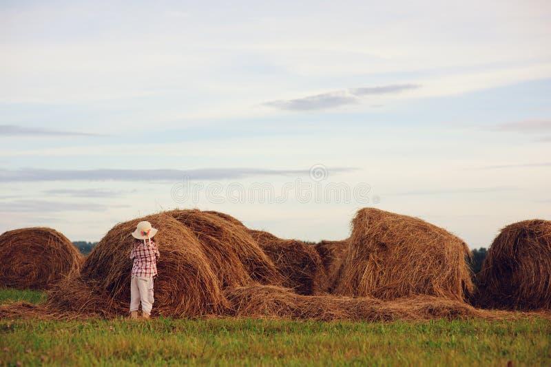 愉快的7岁乡村模式的放松在与干草堆的夏天领域的格子花呢上衣和帽子的儿童女孩 图库摄影