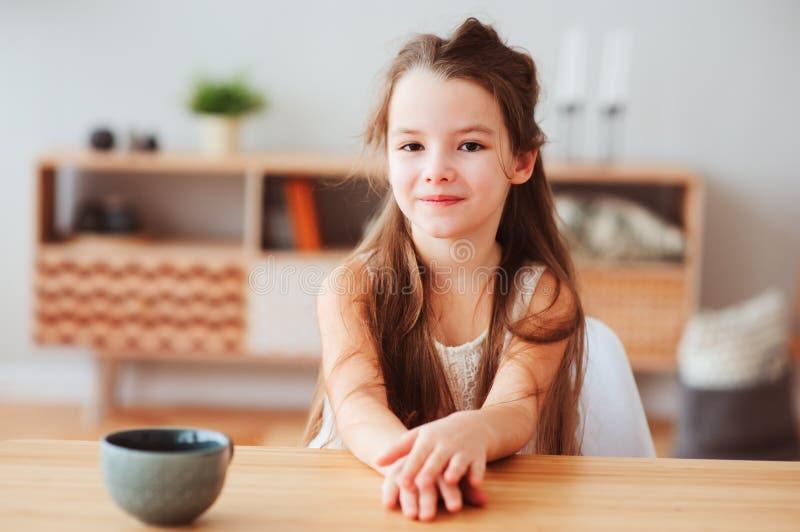 愉快的5岁在家哄骗女孩吃早餐早晨 免版税库存照片