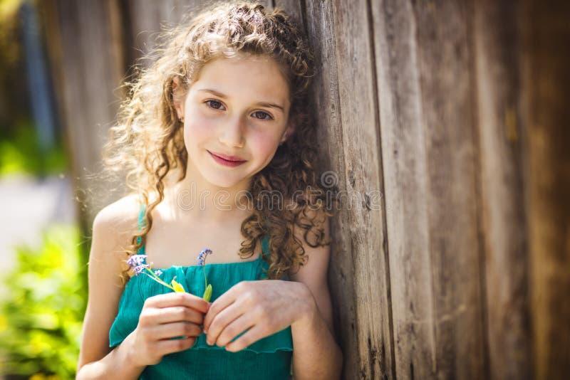 愉快的9岁夏天打击花的女孩 库存图片