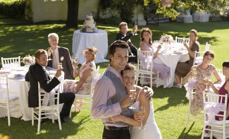 愉快的年轻拥抱在庭院里的新娘和新郎 图库摄影