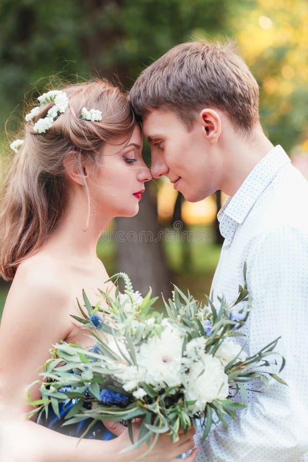 愉快的年轻新婚佳偶夫妇感人的前额在公园 藏品 免版税库存照片