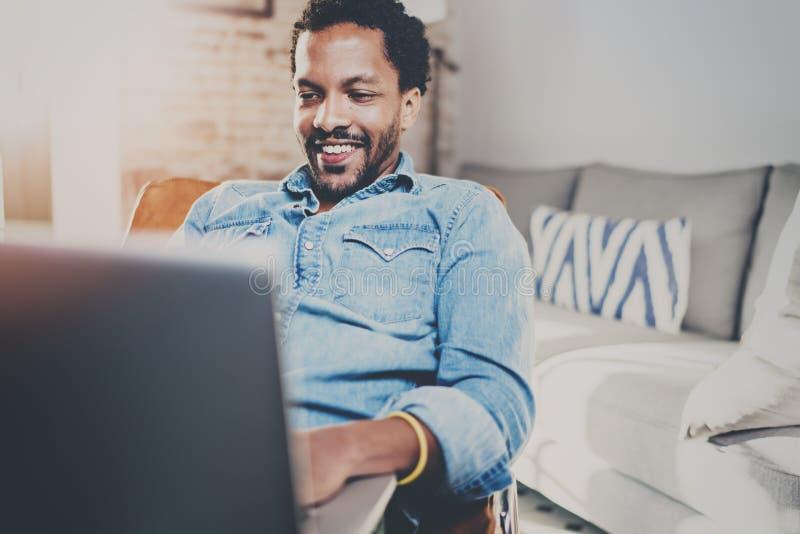 愉快的年轻有胡子的非洲人消费休息时间在家和使用膝上型计算机 享受移动设备的人的概念 库存图片