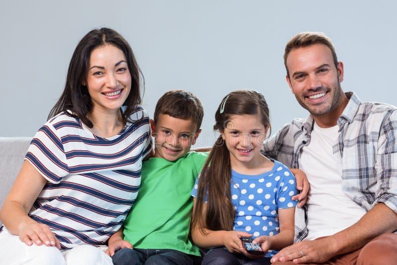 愉快的年轻有他们的两个孩子的家庭观看的电视 库存照片