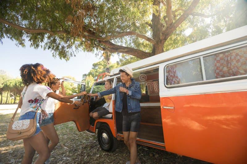 愉快的年轻朋友乘在露营地的露营者货车 免版税图库摄影