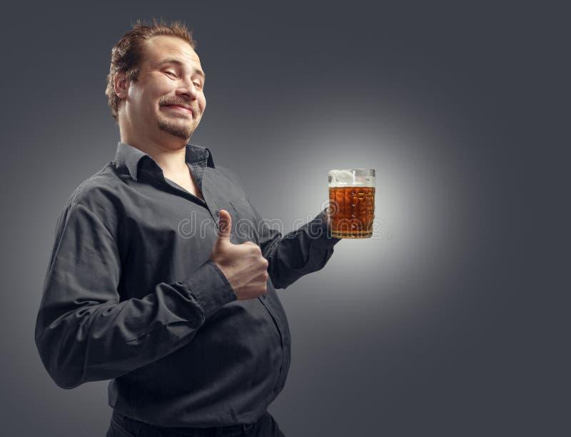 愉快的从杯子的人饮用的啤酒 免版税库存照片