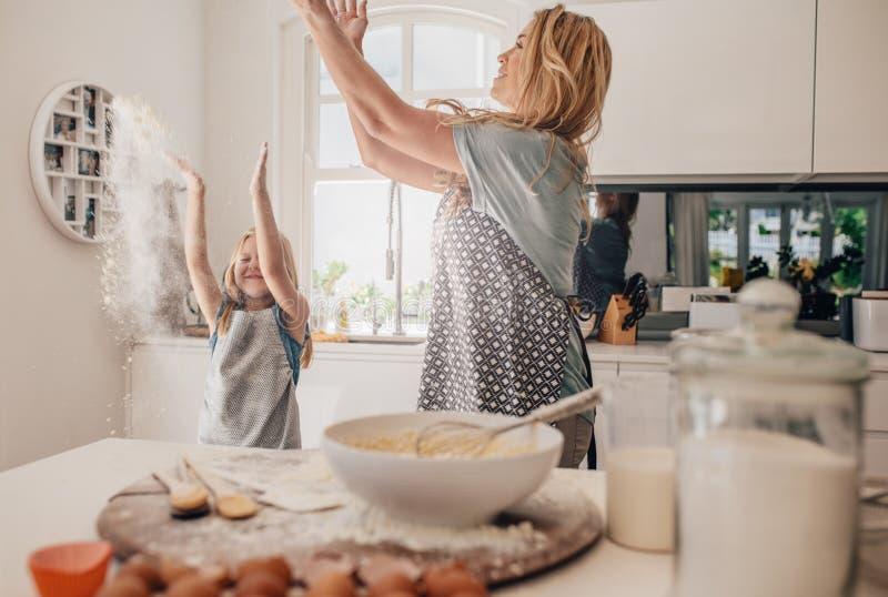 愉快的年轻母亲和女儿获得乐趣在厨房 免版税库存图片