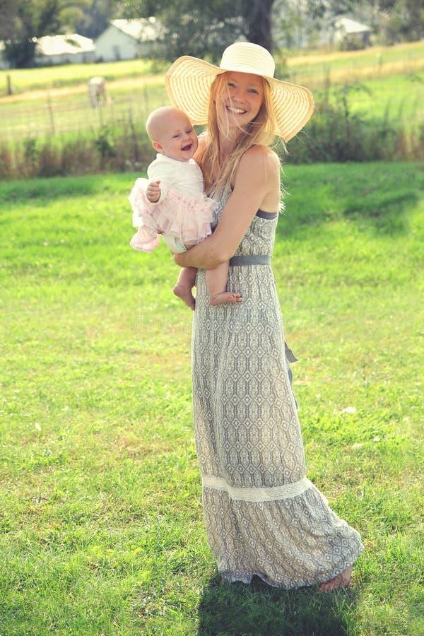 愉快的年轻母亲和婴孩在国家 免版税库存照片