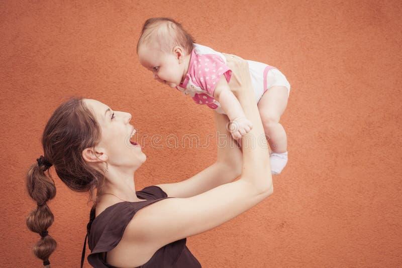 愉快的年轻母亲投掷在背景桔子墙壁上的婴孩 免版税图库摄影