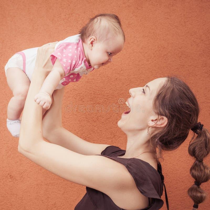 愉快的年轻母亲投掷在背景桔子墙壁上的婴孩 免版税库存图片