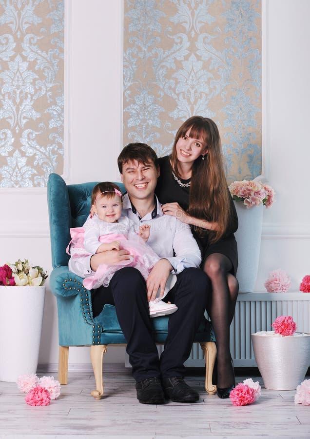 愉快的年轻理想的微笑的家庭在家,母亲、父亲和女儿 免版税库存图片