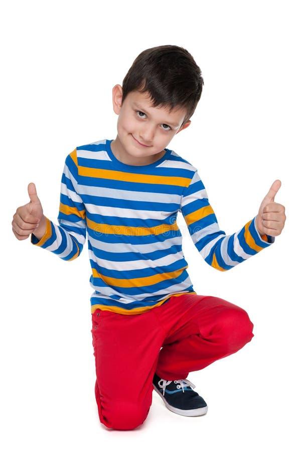 愉快的年轻男孩举行他的赞许 图库摄影