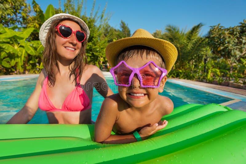 愉快的戴滑稽的太阳镜的母亲和男孩 图库摄影