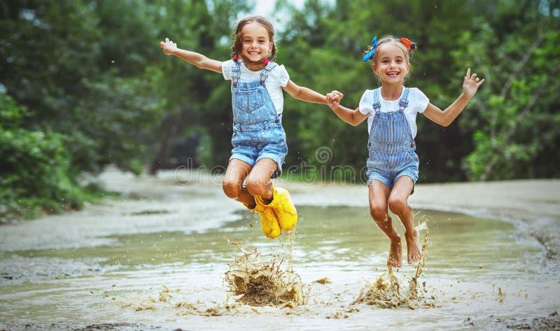 愉快的滑稽的姐妹孪生跳在磨擦的水坑的儿童女孩 免版税库存图片