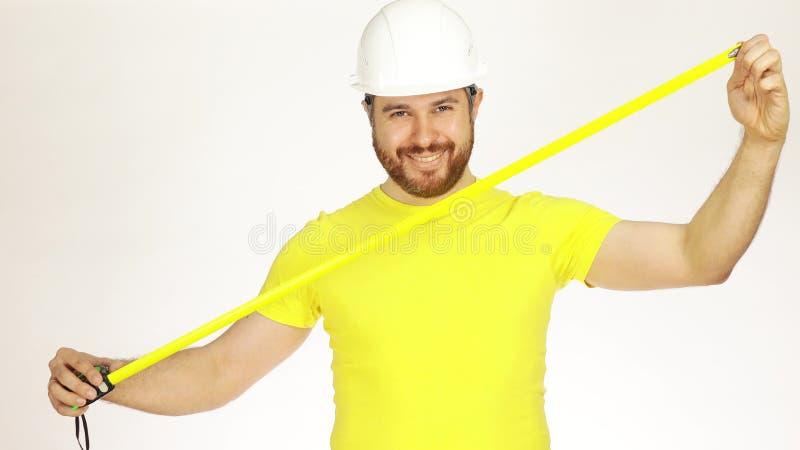 愉快的建筑工程师或建筑师黄色T恤杉和安全帽的使用措施磁带反对白色背景 免版税库存照片