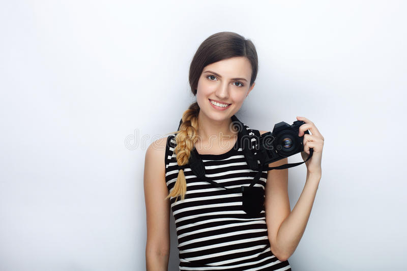 愉快的年轻美丽的妇女画象摆在与黑照片照相机的镶边衬衣的反对演播室背景 图库摄影