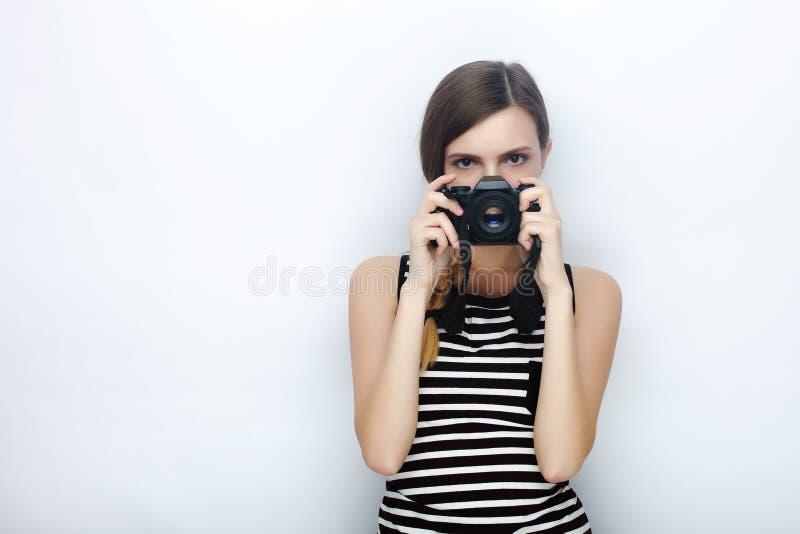 愉快的年轻美丽的妇女画象摆在与黑照片照相机的镶边衬衣的掩藏她的面孔反对演播室背景 免版税库存照片