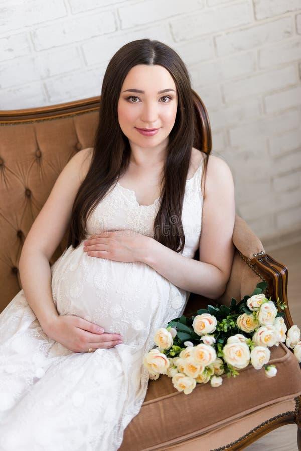 愉快的年轻美丽的孕妇坐葡萄酒沙发机智 免版税库存照片