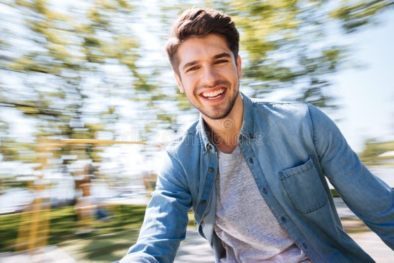 愉快的年轻英俊的人获得乐趣在公园 免版税库存照片