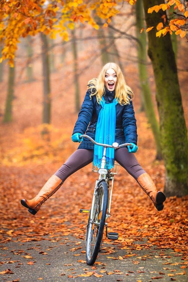 愉快的活跃妇女骑马自行车在秋天公园 库存照片