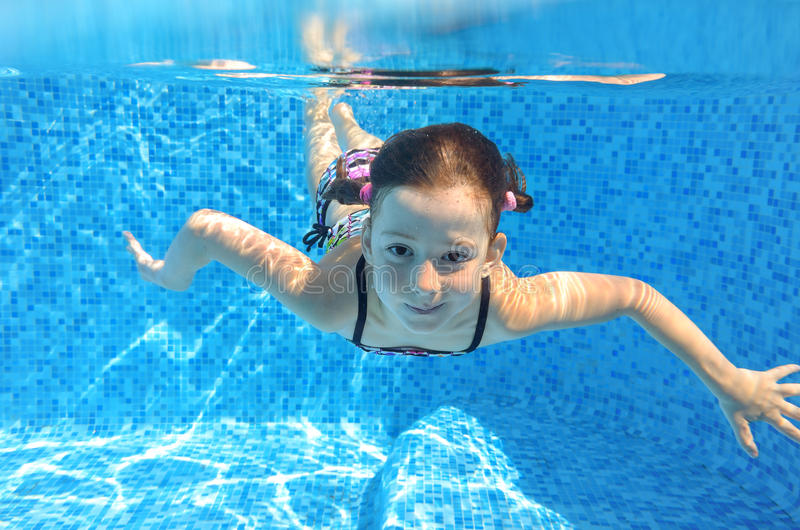 愉快的活跃孩子在水池游泳在水面下 免版税图库摄影