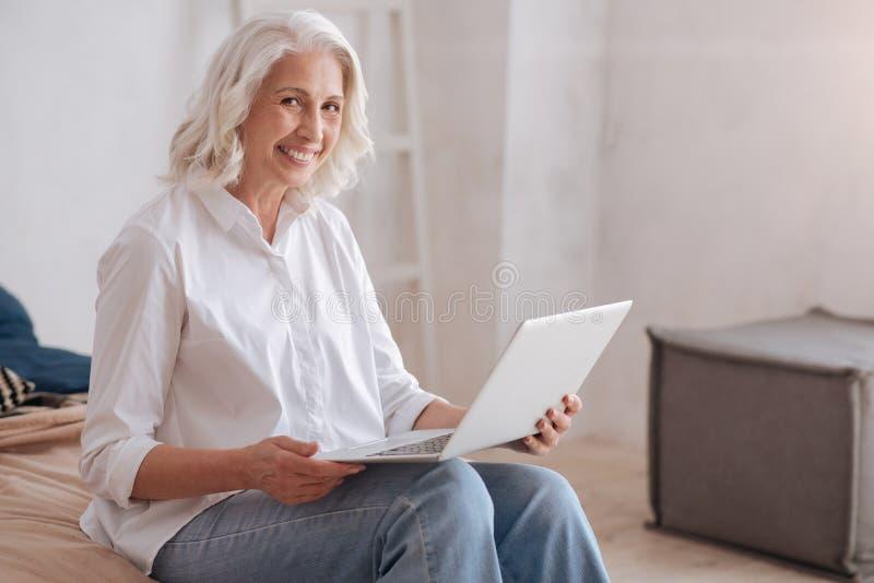 愉快的年迈的妇女坐她的床 免版税图库摄影