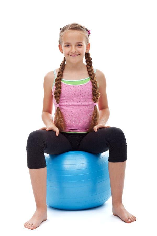 愉快的年轻运动的女孩坐大体操橡胶球 免版税库存图片