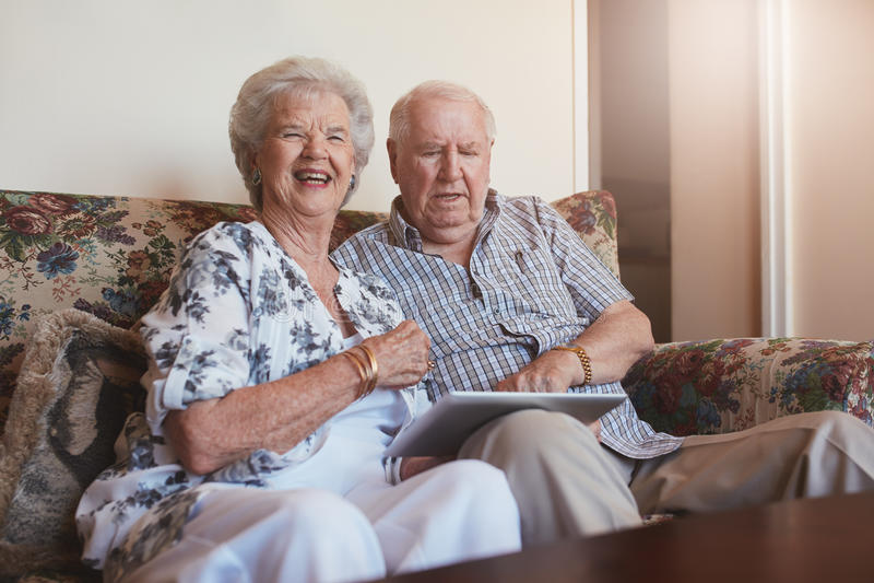 愉快的年长加上数字式片剂在家 库存图片