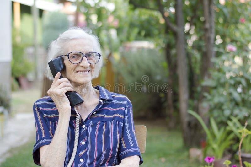 愉快的年长妇女谈话在电话在后院 库存照片