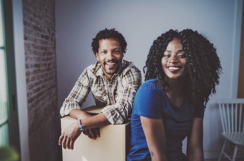 愉快的年轻非洲黑人夫妇移动的箱子到新的公寓里一起和做成功的生活 快乐的系列 免版税库存图片